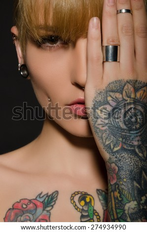 Young blonde with a tattoo on body, dark background - stock photo