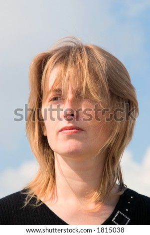 Young blonde woman against cloudy sky