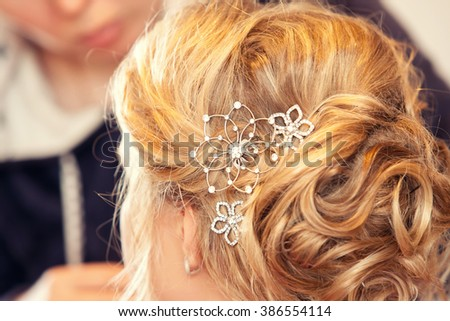 Young blonde woman and jeweler hairpin in the girl's hair