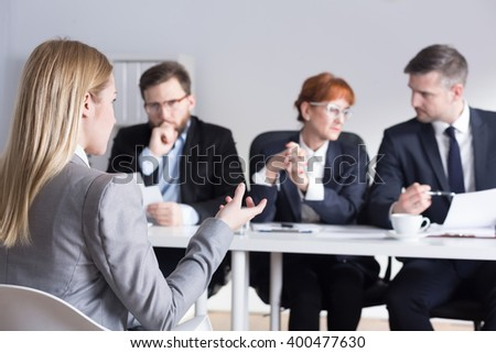 Young blonde woman applying for a job in big corporation. Talking about her experience during interview - stock photo