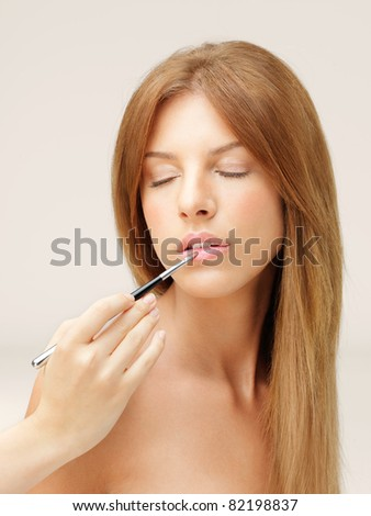 young blonde woman applying lipstick with brush - stock photo
