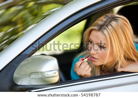Young blonde woman applying makeup while in the car
