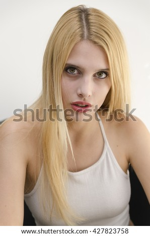 Young blonde woman beautiful green eyes portrait sitting on a sofa - stock photo