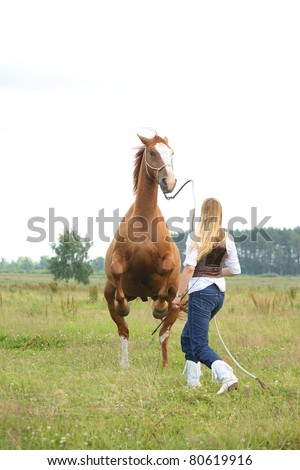 young blonde woman commanding chestnut horse to stand on hind legs