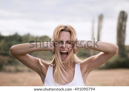 Young blonde woman covering ears with her hands, screaming loudly with visible stress and anger on her face. I do not want to listen to you anymore