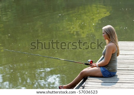 Young blonde woman fishing from pier or dock in river - stock photo