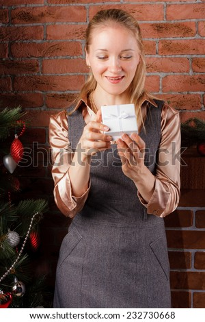 Young blonde woman holding small gift box under the Christmas tree - stock photo