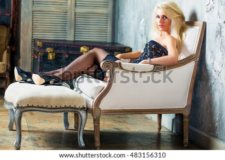Young blonde woman in a sexy black lingerie and high-heel shoes sits in armchair with her feet on footrest in room.