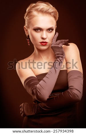 Young blonde woman in black dress and long gloves on dark background toned in marsala color - stock photo
