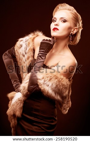 Young blonde woman in black dress and lynx fur with long gloves on dark background toned in marsala color - stock photo