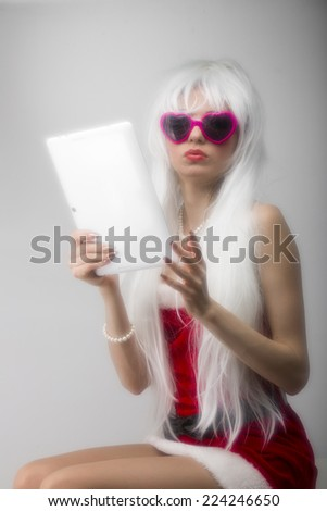 Young blonde woman in pink glasses with a tablet in hands soft effect - stock photo
