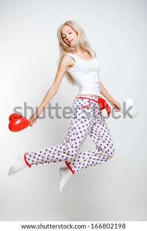 Young blonde woman in pyjamas jumping on gray background with red and white balloons in hands - stock photo