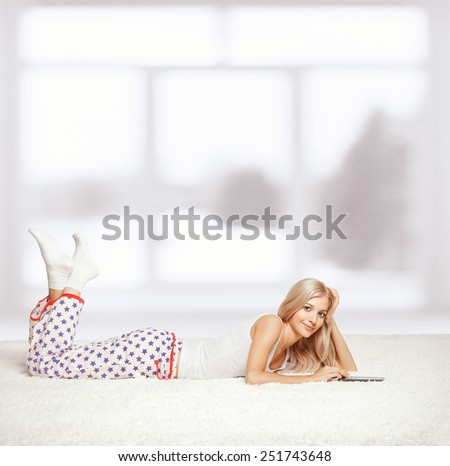 Young blonde woman in pyjamas on white whole-floor carpet reading e-book - stock photo