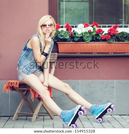 Young blonde woman in roller skates sitting on the chair. Beautiful smiling girl summer portrait  toned with tender summer yellow color. Outdoors. lifestyle - stock photo