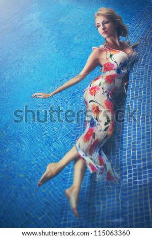 Young blonde woman in the swimming pool, fashion portrait. - stock photo