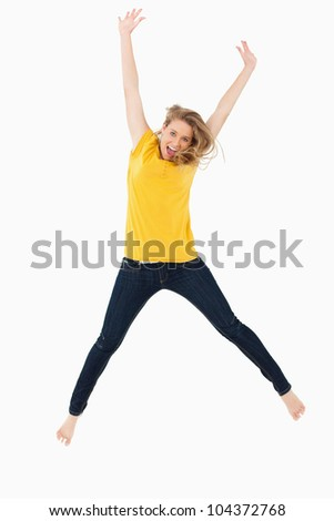 Young blonde woman in yellow shirt jumping against white background - stock photo