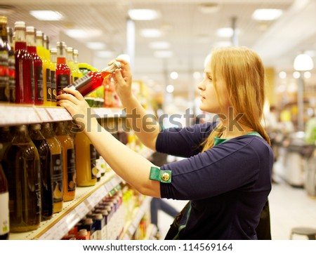 Young blonde woman is choosing juice in the supermarket - stock photo
