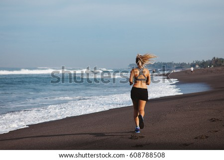 Young blonde woman jogging on the beach, morning work out