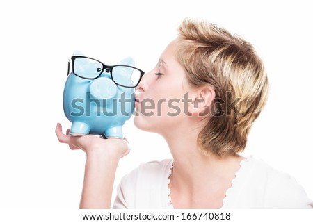 young blonde woman kissing a blue piggy bank on white background - stock photo