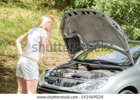 Young blonde woman looking at broken car with open hood. - stock photo