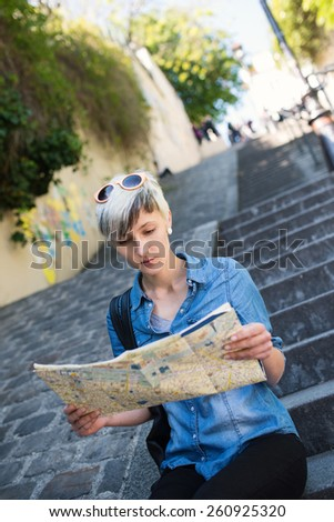 Young blonde woman looking at map of the city in Montmartre. Paris, France.  - stock photo