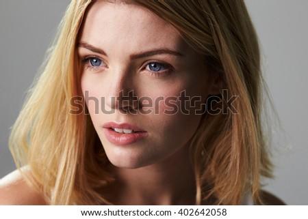 Young blonde woman looking away, close up horizontal - stock photo