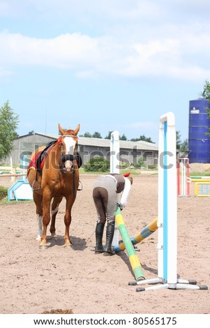 Young blonde woman making a barrier for show jumping and chestnut horse - stock photo