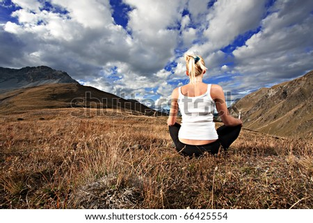 Young blonde woman meditating on a lawn on top of a mountain