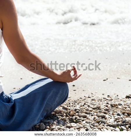 Young blonde woman meditation on the beach - stock photo