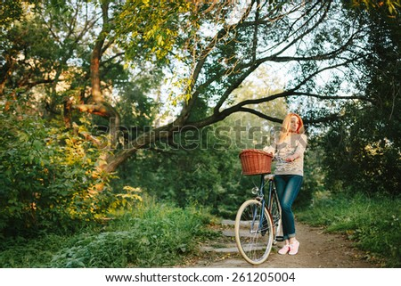 Young blonde woman on a vintage bicycle in the park. Hipster style.