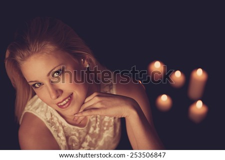 Young blonde woman on black sheets with candles in background
