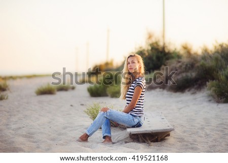 Young blonde woman on the Beach at Sunset, surfer.