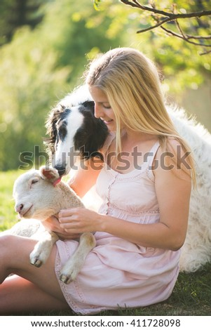 Young blonde woman outdoor portrait with lamb and russian wolfhound dog. Life at the farm. - stock photo