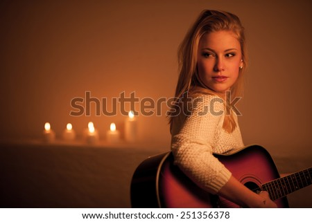 Young blonde woman playing guitar in candle light - stock photo