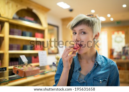 Young blonde woman portrait eating the french pastry macaron inside a typical shop in Paris, France.  - stock photo