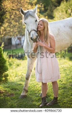 Young blonde woman posing outdoor with white horse.