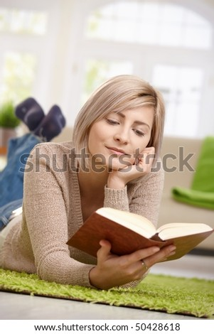 Young blonde woman relaxing on floor at home reading book. Copyspace above. - stock photo