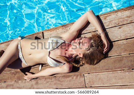 young blonde woman resting near pool in a summer day
