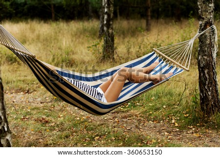 Young blonde woman resting on hammock - stock photo