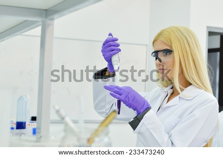 Young blonde woman scientist researcher in the laboratory of the University - stock photo