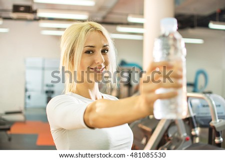 Young blonde woman showing bottle of water in a gym.