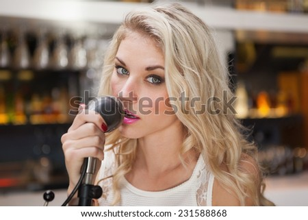 Young blonde woman singing while looking at camera at the nightclub - stock photo