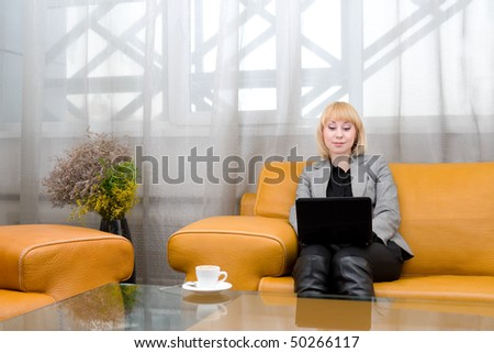 young blonde woman sits on leather sofa with laptop, in front of glass table - stock photo