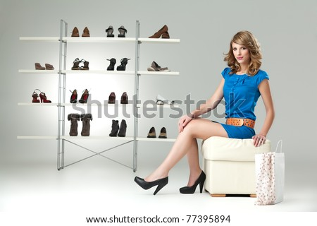 young blonde woman sitting down blue dress