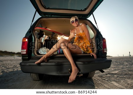 Young Blonde Woman sitting in the back of her truck on the beach - stock photo