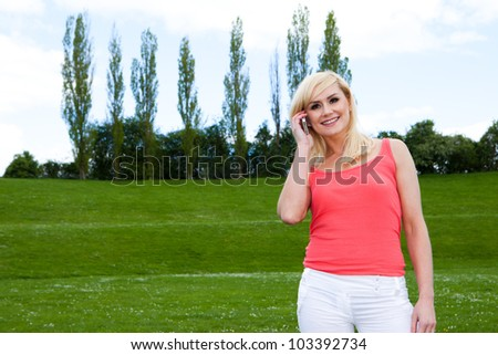 Young blonde woman speaking over the phone outside - stock photo
