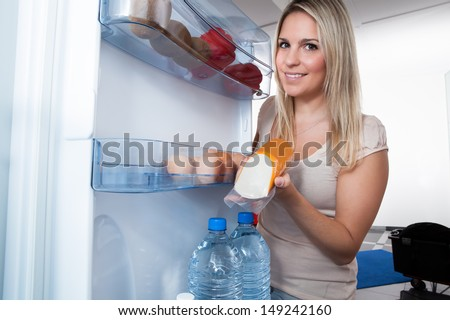 Young Blonde Woman Taking Sausage From Refrigerator At Home