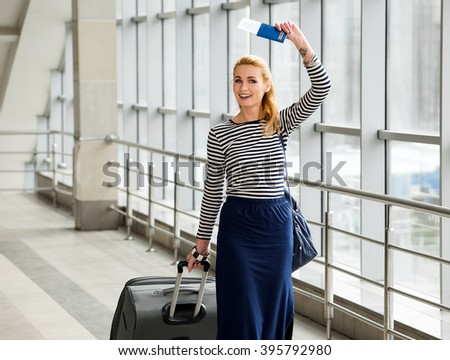 young blonde woman talking on the station with a suitcase and a backpack and holding a passport in their hands. gathered on a trip.