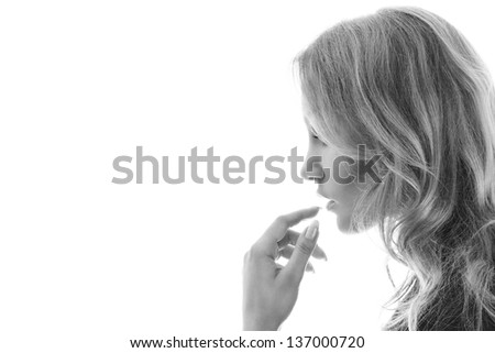 Young blonde woman touching lips close-up portrait isolated on white background - stock photo