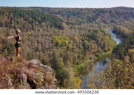 Young blonde woman tourist  in shirt and shorts  on a cliff over the river Berd at fall time. Russia, Siberia, Salair